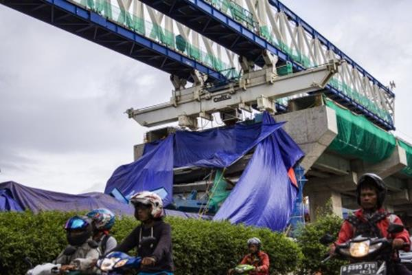 Pengendara melintas di samping proyek Light Rapid Transit (LRT) yang ditutup terpal karena roboh di Jalan Kayu Putih Raya, Pulogadung, Jakarta, Senin (22/1). Proyek LRT yang menghubungkan Kelapa Gading-Velodrome kontruksinya roboh di Jalan Kayu Putih Raya pada Senin (22/1) pukul 00.10 WIB dan mengakibatkan lima orang terluka akibat tertimpa reruntuhan proyek tersebut. ANTARA FOTO - Galih Pradipta