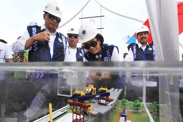 Menteri Keuangan Sri Mulyani (kedua kanan) bersama Menhub Budi Karya Sumadi (kiri), Menteri PUPR Basuki Hadimuljono (kedua kiri) dan Gubernur Sumut Tengku Erry Nuradi (kanan) mengamati miniatur jalur ganda rel layang kereta api, di Medan, Sumatra Utara, Rabu (17/1). - ANTARA/Septianda Perdana