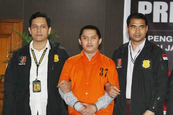 Polisi mengawal tersangka kasus penipuan PT First Travel Andika Surachman (tengah) saat gelar perkara kasus penipuan PT First Travel di Bareskrim Polri, Jakarta, Selasa (22/8). - ANTARA/Reno Esnir