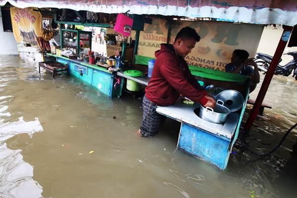 Pedagang memasak saat banjir menggenangi kawasan Tanjung Duren, Jakarta, Selasa (21/2). - Antara/Rivan Awal Lingga