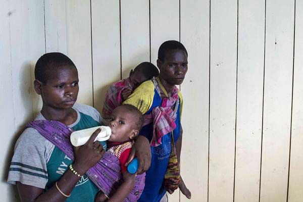 Dua ibu menggendong anaknya saat menunggu antrean berobat di puskesmas Ayam di kampung Bayiwpinam, Distrik Akat, Kabupaten Asmat, Papua, Jumat (26/1). - ANTARA/M Agung Rajasa