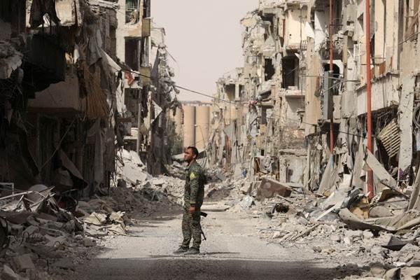 Seorang pejuang dari Pasukan Demokratik Suriah (SDF) berdiri diantara reruntuhan gedung yang hancur di Raqqa, Suriah, Senin (25/9/2017). - Reuters