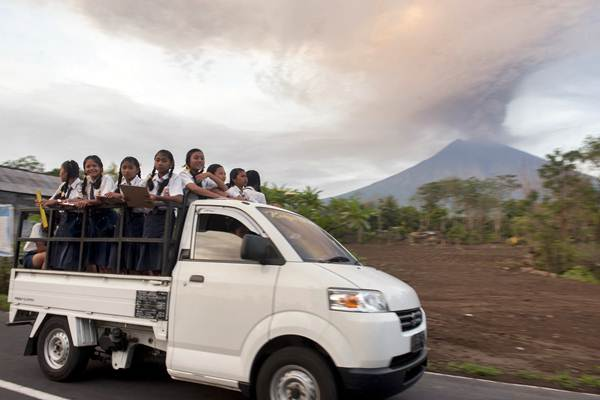 Kendaraan mengangkut siswa dengan latar belakang asap dan abu vulkanik menyembur dari kawah Gunung Agung di Desa Datah, Karangasem, Bali, Senin (27/11). - ANTARA/Nyoman Budhiana