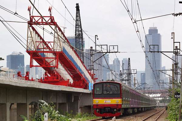 Kereta rel listrik melintas di dekat lokasi launching girder (alat angkat proyek) yang jatuh pada proyek pembangunan jalur ganda kereta ManggaraiJatinegara, di Jatinegara, Jakarta Timur, Minggu (4/2). - JIBI/Dwi Prasetya