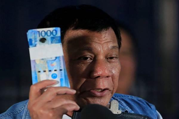 Presiden Filipina Rodrigo Duterte memegang uang peso Filipina untuk pengungsi Marawi saat berkunjung ke pusat Iligan City National School of Fisheries di Iligan City, Filipina pada tanggal 20 Juni 2017. - Reuters