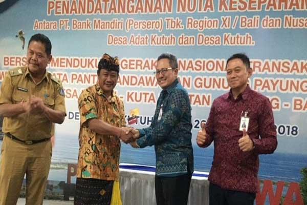 Bendesa Kutuh Made Wena (dua dari kiri) dan Regional CEO PT.Bank Mandiri (Persero) Tbk. Regional XI Bali dan Nusra R. Erwan Djoko Hermawan (dua dari kanan) saat penandatangan nota kesepahaman transaksi non tunai untuk objek wisata Pantai Pandawa