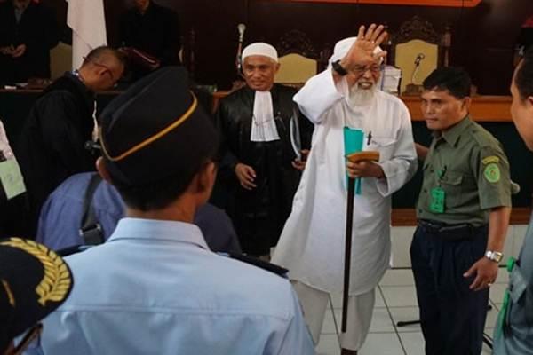 Abu Bakar Ba'asyir nampak melambaikan tangan usai persidangan - Antara
