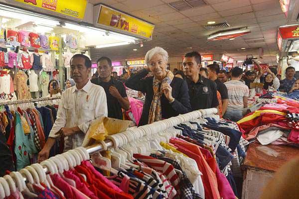 Presiden Joko Widodo (kiri) besama Direktur Pelaksana Dana Moneter Internasional (IMF) Christine Lagarde (ketiga kiri) melakukan blusukan ke Pasar Tanah Abang Jakarta, Senin (26/2). - ANTARA/Wahyu Putro A