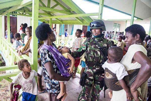 Prajurit TNI berbincang dengan warga saat menunggu antrean berobat di puskesmas Ayam di kampung Bayiwpinam, Distrik Akat, Kabupaten Asmat, Papua, Jumat (26/1). - ANTARA/M Agung Rajasa