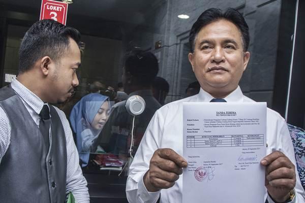 Ketua Umum Partai Bulan Bintang Yusril Ihza Mahendra (kanan) menunjukan berkas tanda terima seusai mengajukan permohonan uji materi UU Pemilu di Mahkamah Konstitusi, Jakarta, Selasa (5/9). - ANTARA/Aprillio Akbar