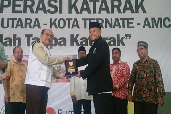 Ketua Baznas, Bambang Sudibyo (kiri kedua), menyerahkan plakat kepada Ketua Dewan Pembina Asia Muslim Charity Foundation, Ahmad Yaman (kanan ketiga) di tempat operasi katarak gratis secara masal di Ternate, Maluku Utara, Kamis (8/3/2018). - Istimewa