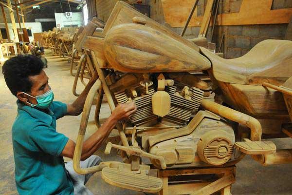 Pekerja menghaluskan komponen badan replika motor Harley Davidson yang terbuat dari kayu jati, di Kemiri, Mojosongo, Boyolali, Jawa Tengah, Rabu (14/6). Berbagai jenis replika motor besar diproduksi dari bahan kayu jati yang dijual ke berbagai negara seperti Prancis, Inggris, dan Belanda. - Antara/Aloysius Jarot Nugroho