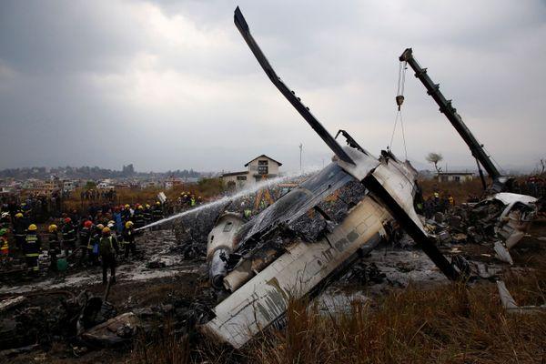 Puing pesawat US-Bangla Airlines yang jatuh terbakar di Bandara Internasional Tribuvhan di Kathmandu, Nepal pada Senin (12/3). - Reuters/Navesh Chitrakar