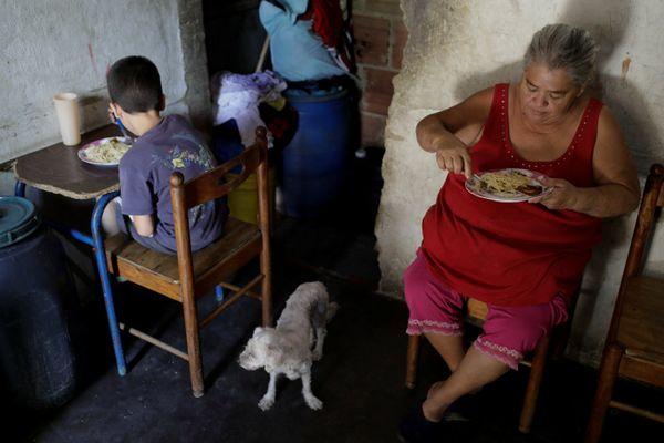 Warga Caracas mengonsumsi pasta dari paket bantuan makanan yang dikirim Pemerintah Venezuela pada Jumat (9/3). - Reuters/Marco Bello