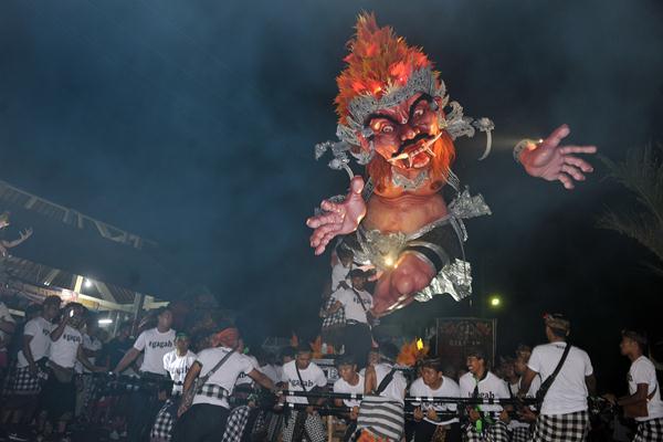 Para remaja mengarak Ogoh-Ogoh atau boneka raksasa yang melambangkan sifat buruk dalam parade Ogoh-Ogoh 2017 menjelang Hari Raya Nyepi Tahun Saka 1939 di Desa Tegallalang, Gianyar, Bali, Minggu (26/3). Arak-arakan Ogoh-Ogoh tersebut untuk menetralisir hal-hal negatif dan mengembalikannya ke asalnya sehingga Hari Raya Nyepi dapat dilaksanakan dengan penuh keheningan dan kedamaian. ANTARA FOTO - Nyoman Budhiana