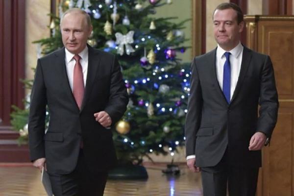 Presiden Rusia Vladimir Putin (ki) dan Perdana Menteri Dmitry Medvedev berjalan sebelum sebuah pertemuan dengan anggota pemerintahan di Moskow, Rusia, Selasa (26/12/2017).  - Sputnik