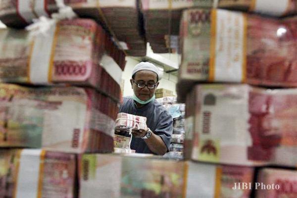 Karyawan menata uang rupiah. - JIBI/Abdullah Azzam