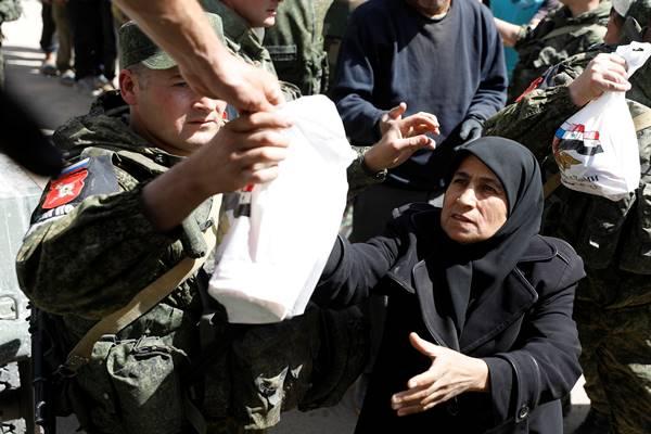 Seorang wanita yang melarikan diri dari Ghouta timur menerima bantuan dari pasukan Rusia di sebuah tempat penampungan di Adra, dekat Damaskus, Suriah, 20 Maret 2018. - Reuters
