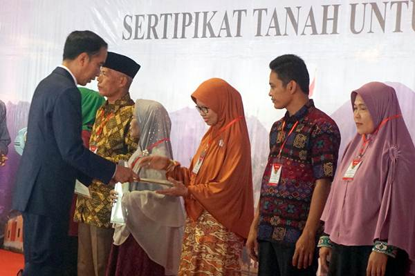 Presiden Joko Widodo memberikan sertifikat tanah secara simbolis kepada perwakilan warga di Sentul, Kabupaten Bogor, Jawa Barat, Selasa (6/3/2018). - ANTARA/Yulius Satria Wijaya