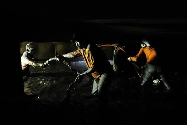 Seorang pekerja membersihkan kulit kabel listrik yang menutup saluran air di Jalan Merdeka Selatan, Jakarta, Senin (29/2). - Antara