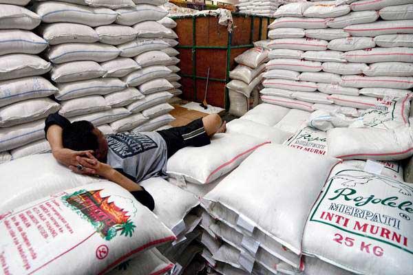 Pekerja beristirahat di atas tumpukan karung beras di Pasar Induk Beras Cipinang, Jakarta Timur, Jumat (19/1). - ANTARA/Sigid Kurniawan