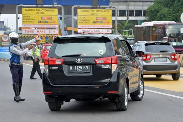 Sejumlah Polisi dan Dishub mengarahkan kendaraan roda empat berplat nomor ganjil berputar balik keluar dari gerbang tol Bekasi Barat 1 di Bekasi, Jawa Barat, Senin (12/3). Kementerian Perhubungan melalui Badan Pengelola Transportasi Jabodetabek (BPTJ) memberlakukan sistem ganjil genap di pintu tol Bekasi Barat dan Bekasi Timur arah Jakarta mulai Senin (12/3) pukul 06.00 - 09.00 WIB setiap hari Senin -Jumat. ANTARA FOTO - Widodo S Jusuf