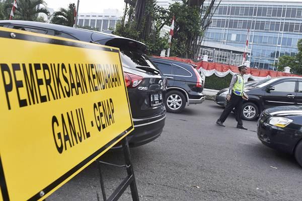 Polisi memeriksa pelat nomor mobil di kawasan pembatasan lalu lintas ganjil-genap di sekitar Bundaran Senayan, Jakarta, Selasa (30/8). - Antara/Hafidz Mubarak A