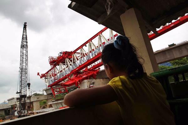 Warga mengamati launching girder (alat angkat proyek) yang jatuh pada proyek pembangunan jalur ganda kereta ManggaraiJatinegara, di Jatinegara, Jakarta Timur, Minggu (4/2). - JIBI/Dwi Prasetya