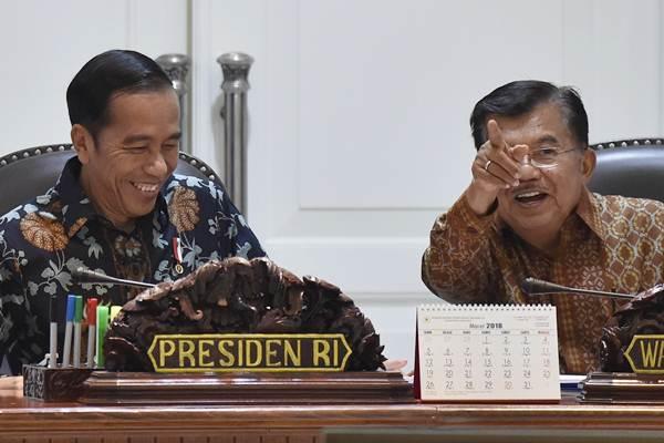 Presiden Joko Widodo (kiri) berbincang dengan Wakil Presiden Jusuf Kalla (kanan) sebelum memimpin rapat terbatas tindak lanjut kebijakan satu peta di Kantor Presiden, Jakarta, Senin (5/2). - ANTARA/Puspa Perwitasari