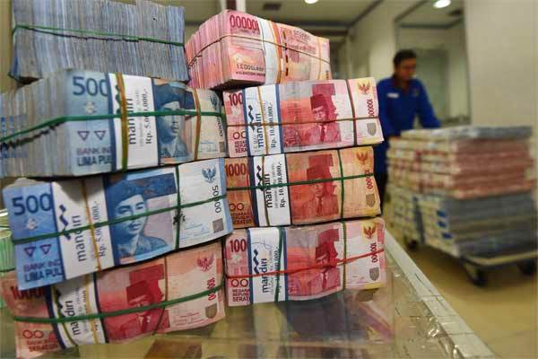 Petugas memindahkan uang - Antara/Akbar Nugroho Gumay