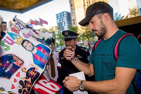 Bintang FC Barcelona dan Timnas Uruguay Luis Suarez memenuhi keinginan fans yang menyambut kedatangannya dengan memberikan tanda tangan. Uruguay berpartisipasi dalam China Cup. - Daily Mail