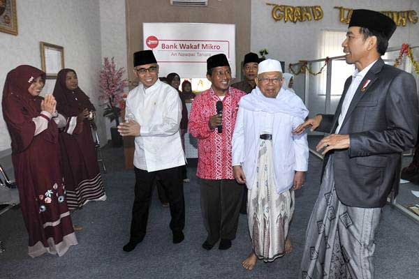 Presiden Joko Widodo (kanan) didampingi Ketua MUI KH Maruf Amin (kedua kanan), Ketua Dewan Komisioner OJK (Otoritas Jasa Keuangan) Wimboh Santoso (ketiga kiri) serta Ketua Bank Wakaf Mikro Tanara Syamsudin (tengah) berdialog dengan petugas konter Bank saat Peluncuran Bank Wakaf Mikro Tanara di Serang, Banten, Rabu (14/3/2018). - ANTARA/Asep Fathulrahman