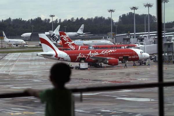 Seorang anak memperhatikan sejumlah pesawat yang tengah parkir di Bandara Intenasional Changi di Singapura - Reuters/Edgar Su