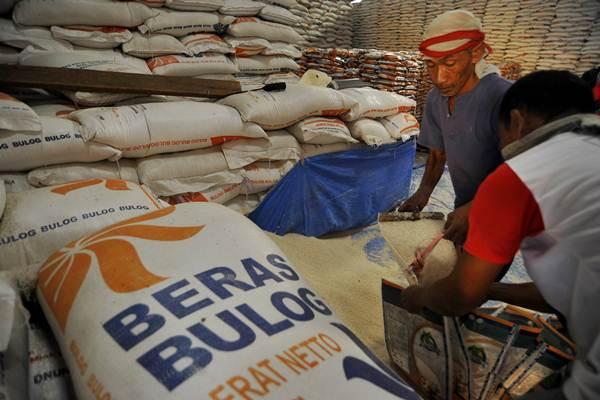 Pekerja mengemas beras di gudang Bulog Serang, Banten, Senin (11/9). - ANTARA/Asep Fathulrahman
