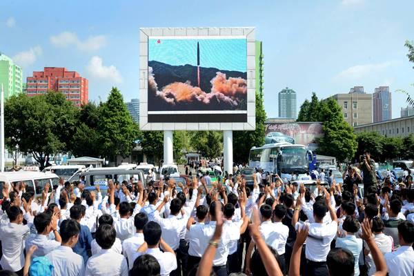 Warga Korea Utara menonton peluncuran uji rudal balistik antarbenua Hwasong-14 . Foto dirilis Korea Utara News Agency (KCNA). - Reuters