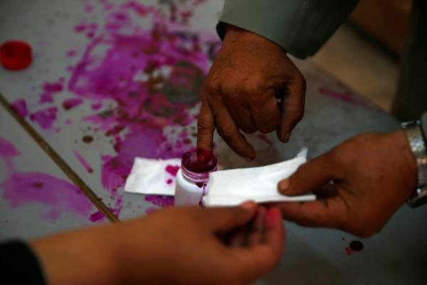 Seorang pemilih mencelupkan jarinya ke tinta saat berlangsung Pemilihan Presiden Mesir di Kairo, 27 Maret 2018. - Reuters