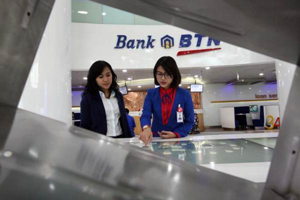 Karyawati PT Bank Tabungan Negara Tbk memberikan penjelasan mengenai produk perbankan kepada nasabah. - JIBI/Dedi Gunawan