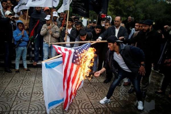 Warga Palestina membakar bendera Israel dan Amerika Serikat dalam sebuah demonstrasi terhadap niat Amerika Serikat memindahkan kedubes mereka ke Yerusalem dan mengenali Yerusalem sebagai ibukota Israel, di Kota Gaza, Rabu (6/12/2017). - Reuters
