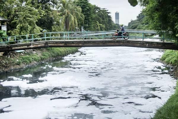 Pengendara sepeda motor melintasi jembatan kali Sunter yang dipenuhi busa di Kelapa Gading Barat, Jakarta, Rabu (21/3). Timbulnya busa tersebut dari pembuangan limbah rumah tangga dan industri. ANTARA FOTO - Aprillio Akbar