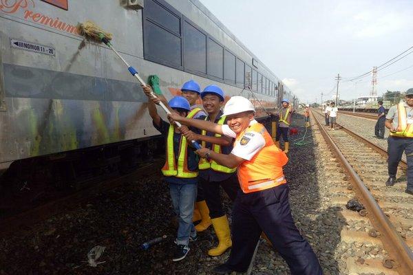 Manajer Humas PT KAI Daops IV, Suprapto (kanan), tengah membersihkan rangkaian KA Tawang Jaya Premium Reguler di Stasiun Tawang, Semarang, Rabu (4/4/2018). - Ist