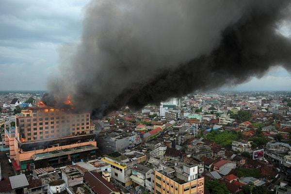 Asap membumbung tinggi dari Hotel Novita yang terbakar di kawasan padat pertokoan di Jambi, Senin (9/4). - Antara/Wahdi Septiawan