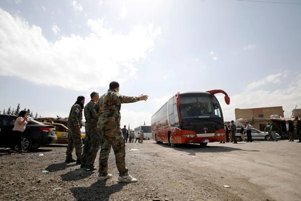 Pemberontak Suriah dan keluarganya meninggalkan kamp Wafideen di tepi Douma menggunakan bus, 9 April 2018. - Reuters