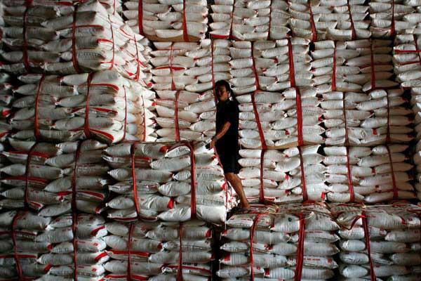 Seorang pekerja berdiri di antara tumpukan karung gula mentah. - Bloomberg