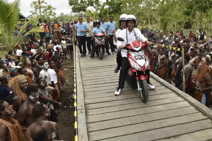 Presiden Joko Widodo berboncengan dengan Ibu Negara Iriana Joko Widodo menggunakan motor listrik menyapa warga Asmat saat kunjungan kerja di Kampung Kaye, Distrik Agats, Kabupaten Asmat, Papua, Kamis (12/4/2018). - Antara/Puspa Perwitasari