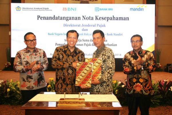 Wakil Direktur BNI Herry Sidharta dan Direktur Jenderal Pajak Robert Pakpahan bersalaman seusai menandatangani nota kesepahaman di Jakarta, Rabu (18/4/2018). (Bisnis - Abdul Rahman)