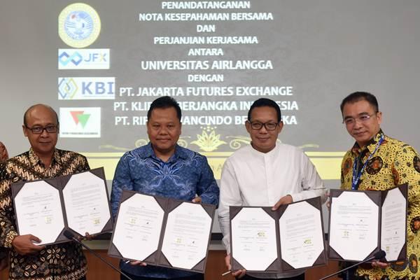 Wakil Rektor IV Universitas Airlangga Junaidi Khotib (kedua kanan) bersama Plt. Dirut PT Kliring Berjangka Indonesia Fajar Wibhiyadi (kiri), dan Dirut PT Rifan Financindo Berjangka Ovide Decroli (kedua kiri), serta Dirut PT Bursa Berjangka Jakarta Stephanus Paulus Lumintang (kanan) memperlihatkan dokumen kesepakatan terkait 'Futures Trading Learning Center' di Surabaya, Jumat (20/4/2018). - ANTARA/Zabur Karuru