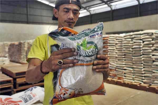 Pekerja memegang beras Bulog kualitas super kemasan 5 kilogram di Gudang Bulog Serang, Banten, Selasa (16/5). - Antara/Asep Fathulrahman