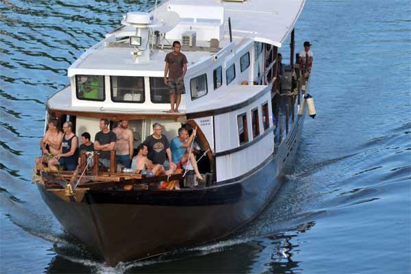 Wisatawan asing berada di haluan kapal, sepulangnya dari Kepulauan Mentawai saat melintas di Sungai Batang Arau, Padang, Sumatra Barat, Minggu (4/6). - Antara/Iggoy el Fitra