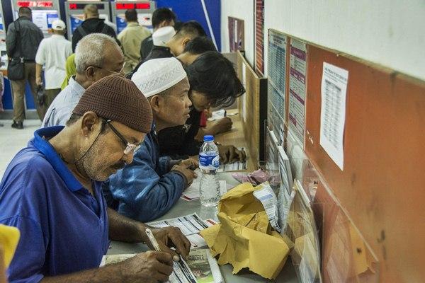 Calon penumpang mengisi formulir pemesanan tiket kereta api di Stastiun Pasar Senen, Jakarta, Jumat (17/3). - Antara/Aprillio Akbar