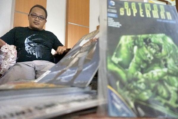 Komikus Ardian Syaf berpose dengan latar depan buku gambar animasi bercerita produksi perusahaan komik internasional Marvel Comics dan DC Comics di Desa Tenggur, Tulungagung, Jawa Timur, Kamis (13/4). - Antara/Destyan Sujarwoko
